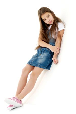 Foto de Little girl in a short denim dress. - Imagen libre de derechos