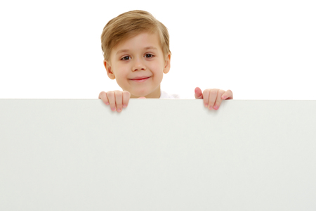 Photo for A little boy is looking from behind an empty banner. - Royalty Free Image