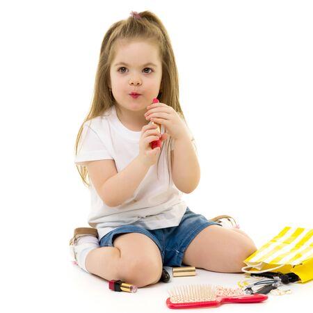 Photo pour Little girl paints lips with moms lipstick. - image libre de droit