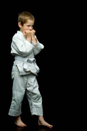 Foto de A little boy in a white kimono fulfills blows - Imagen libre de derechos