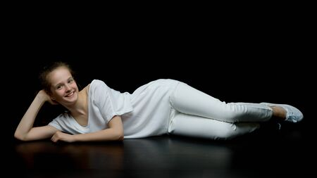 Photo pour Cute little girl lying on the floor in the studio on a black bac - image libre de droit