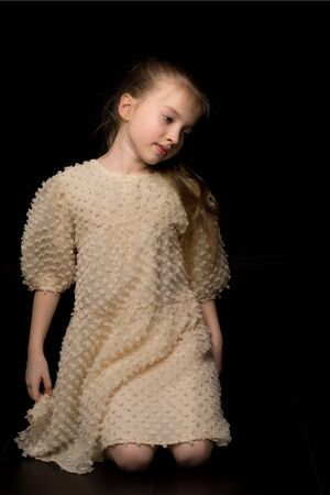 Photo pour A little girl is sitting in the studio on the floor on a black b - image libre de droit
