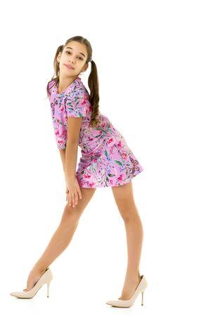 Foto de Cheerful little girl in large shoes taken from her mother. - Imagen libre de derechos