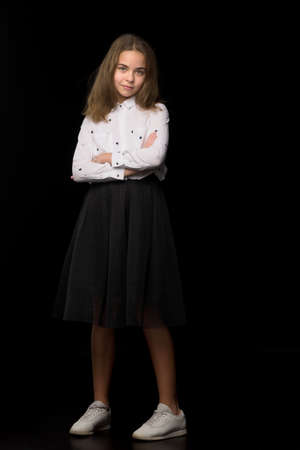 Fashionable girl teenager studio photo on a black background.