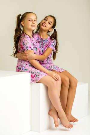 Foto de Two little girls posing in the studio on white cubes - Imagen libre de derechos
