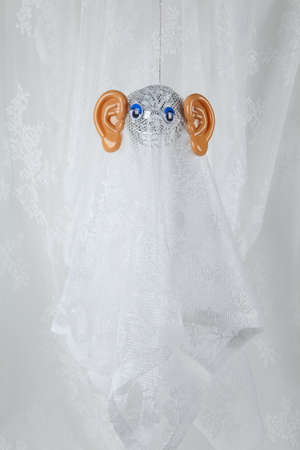 Photo pour Lace curtain ghost made with a disco ball and big plastic ears. Offbeat humor and pop atmosphere. minimal color still life photography - image libre de droit
