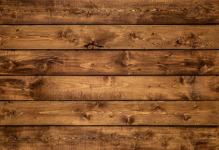 Medium brown wood texture background viewed from above. The wooden planks are stacked horizontally and have a worn look. This surface would be great as design element for a wall, floor, table etc