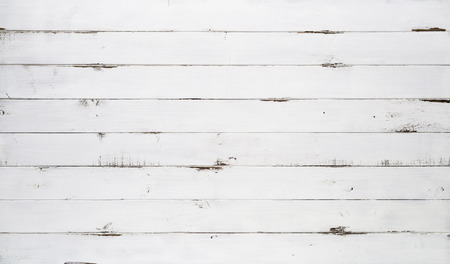 Distressed white wood texture background viewed from above. The wooden planks are stacked horizontally and have a worn look.