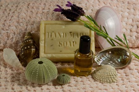 Handmade bath soap and fragrant oil on pink towel