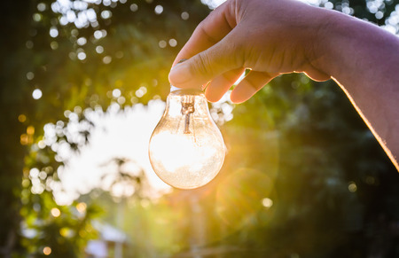 Photo pour and holding a light bulb with sunset power concept - image libre de droit