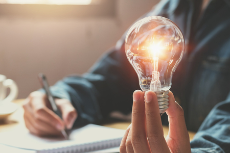 Photo pour new idea and creative concept for business woman hand holding light bulb - image libre de droit