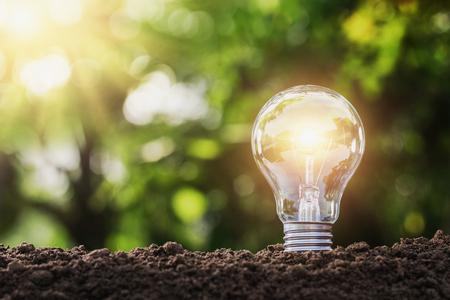 Foto de concept saving energy lightbulb with solar power in nature - Imagen libre de derechos