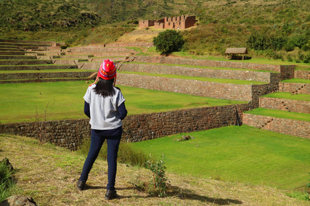 Photo for One female tourist looking at the impressive Inca agricultural and irrigation ruins of Tipon in the Sacred Valley, Cusco region, Peru - Royalty Free Image