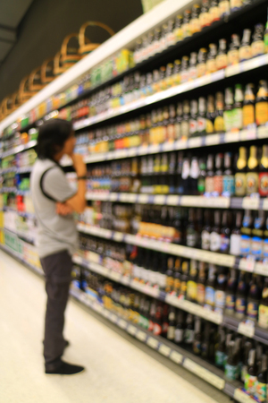 Vertical photo of blurred young man choosing something at grocery shelf in the retail store