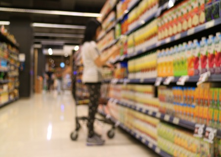 Out of focus shot of a woman with shopping cart selecting goods from the shelf in grocery store