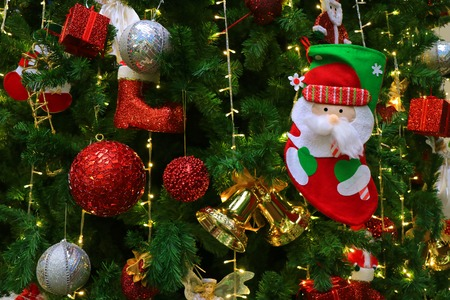 Photo pour Santa Claus Christmas Sock with Many of Vivid Colored Ornaments Hanging on a Sparkling Christmas Tree - image libre de droit