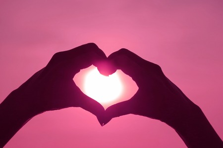 Photo for Pink Colored silhouette of female's hand posing LOVE HEART sign against shiny sun - Royalty Free Image