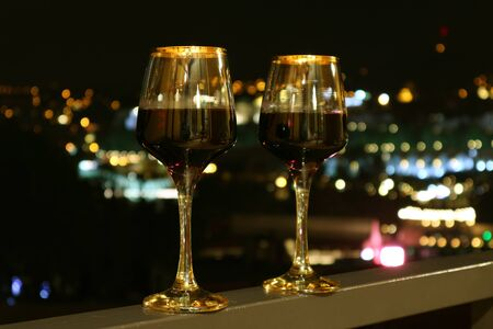 Photo for Two Wine Glasses on the Balcony with Blurry City Night View in the Background - Royalty Free Image