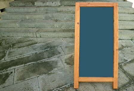 Photo pour Blank wooden standing board on stone paved floor with copy space - image libre de droit