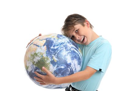 A young boy with his hands hugging the world earth ball.  He is leaning his head into the earth affectionately and smiling.  Concept environmental protection, world care, travel eco-tourism, etc