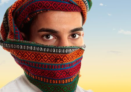 An arab middle eastern man wearing a coloured omani royal keffiyeh which can also be worn like a turban