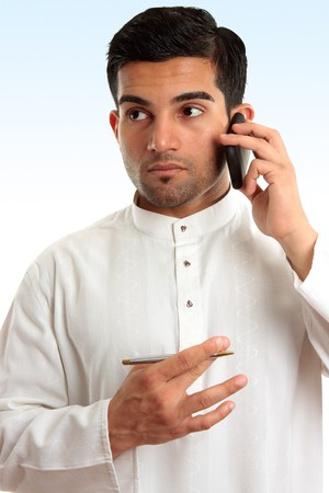 Ethnic mixed race businessman wearing traditional robe is using a mobile phone and looking sideways.
