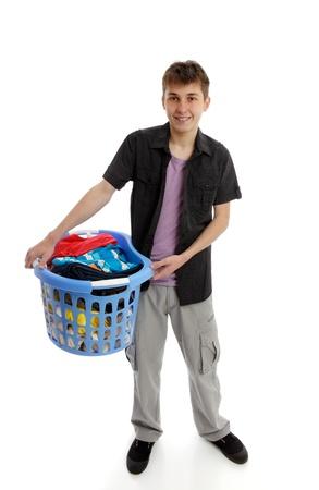 A teenage boy holding a basket of laundry.  White background.