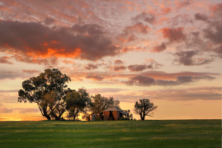 Australian outback sunset.  Old farm house, crumbling walls and verandah with two water tanks out back sits abandoned on a hill at sunset. The last sun rays stretching across the landscape painting the grass in dappled light and edging the tanks and house
