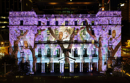 SYDNEY, AUSTRALIA - JUNE 2, 2015;  Customs House is one of the buildings brought to life in vivid colours, patters and imagery during Vivid Sydney annual festival event.   Owls and wisteria on display.