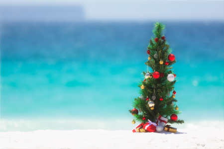 Foto de Christmas tree decorated with colourful baubles and presents underneath it, stands on a beautiful sandy beach with background blur of the ocean and sky.  - Imagen libre de derechos
