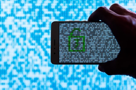 Photo pour Hand holding a smartphone with a locker unlocked against binary code on screen - image libre de droit
