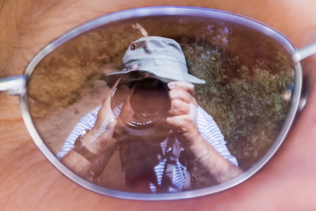 Mirror image of a photographer taking a picture of a Monarch butterfly on his own hat, using the reflection in the lens a woman's glasses