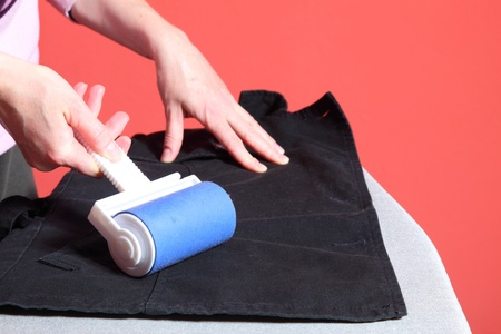 Woman hand cleaning dust with lint roller