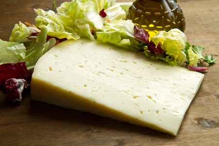 Asiago cheese with fresh salad on wooden table