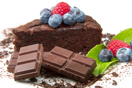 Piece of chocolate cake with fresh berry on white background