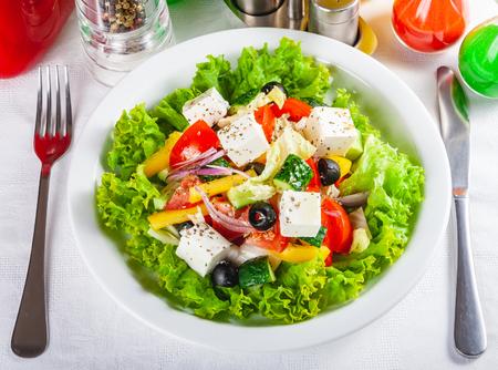 Photo pour Greek salad with vegetables on white plate. Close up - image libre de droit