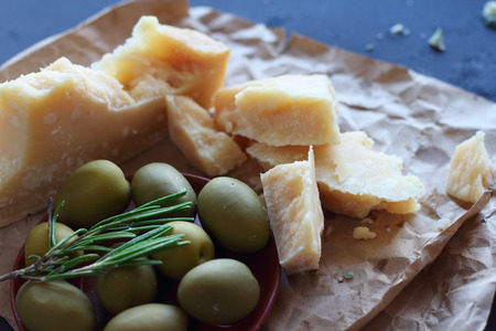 Parmesan cheese, rosemary and olives on brown paper composition