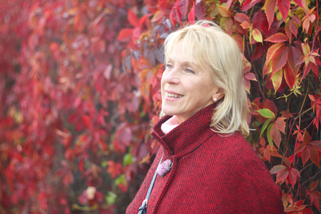 Happy smiling senior woman in autumn park over red leaves background