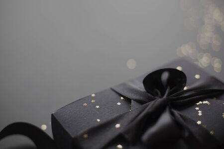 Photo for Black friday gift, paper box with silk ribbon bow on black paper background with copy space for text - Royalty Free Image