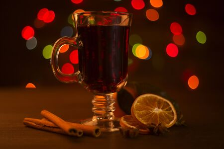 Photo pour Mulled wine with cinnamon sticks and orange over holiday christmas lights background - image libre de droit