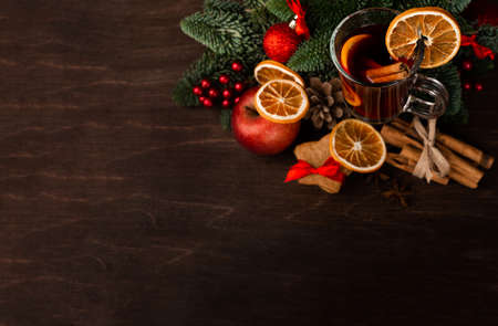 Photo pour Mulled wine with cinnamon sticks orange fir tree branch and baubles Christmas composition over dark wooden background - image libre de droit
