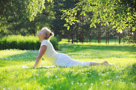 Photo for Beautiful mature woman practice yoga in summer park - Royalty Free Image