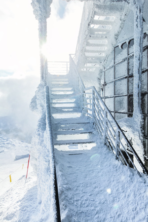 Snow and ice covered stairs and windows at top of mountain Chopok ski resort, with strong sun backlight in background illustrating extreme cold in the winter. Jasna, Slovakia.