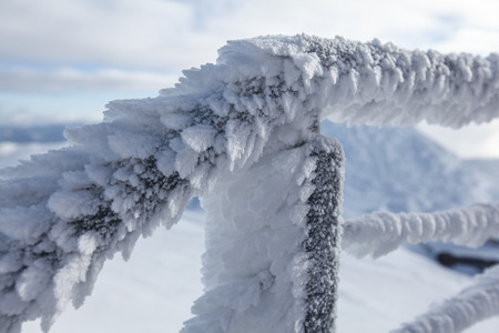 Snow and ice covered stairs fence illustrating extreme cold in the winter.