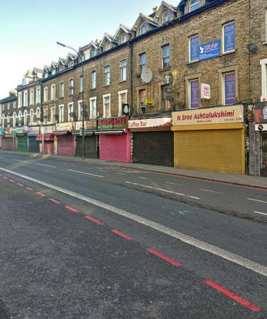 London, United Kingdom - March 31, 2020: Line of shops with shutters closed on Lee High street during coronavirus outbreak. These are usually open even on Sundays but were forced to close due to virus