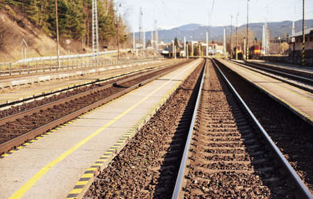 Photo pour Empty train station in small city on sunny day, shallow depth of field photo, focus on concrete platform and steel rails foreground - image libre de droit