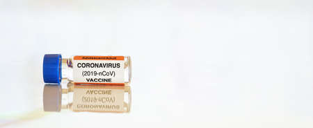 Photo pour Coronavirus Covid-19 vaccine concept - small glass vial with blue cap on white table, closeup detail wide banner space for text right side (sticker is own design  with dummy data, not a real product) - image libre de droit