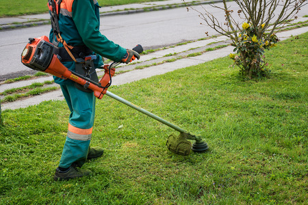 Photo for Man in overall and safety helmet trims overgrown grass by grass cutter - Royalty Free Image