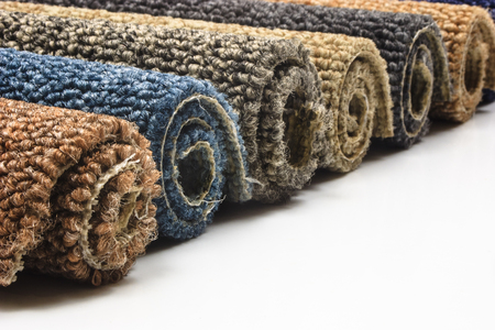 Colorful carpet rolls on white background