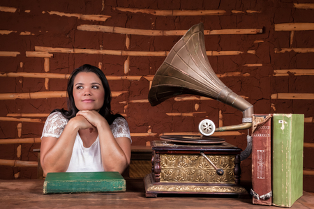 A girl listening to music on an old gramophone with some album discs on the table